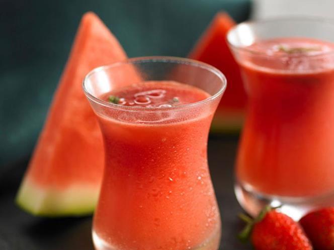 SANDIA 3 - Un smoothie es una bebida cremosa que se elabora con trozos de fruta mezclados con zumo, productos lácteos (leche, helado, yogurt) y en hielo.  Necesitas: media sandía cortada en trocitos, 200 gramos de hielo, 2 fresas, 4 cucharadas de zumo de limón, azúcar al gusto.  Bate todos los ingredientes hasta obtener una consistencia suave. Decora la copa con una rajita de sandía.